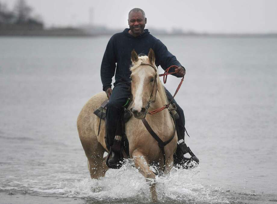 Despite a cold rain, Ricky Izzard, of Oxford, enjoys his final horseback ride of the season at Jennings Beach in Fairfield, Conn. on Sunday, March 31, 2019. Dogs and horses are allowed on Fairfield town beaches from October 1 until March 31. Photo: Brian A. Pounds, Hearst Connecticut Media / Connecticut Post