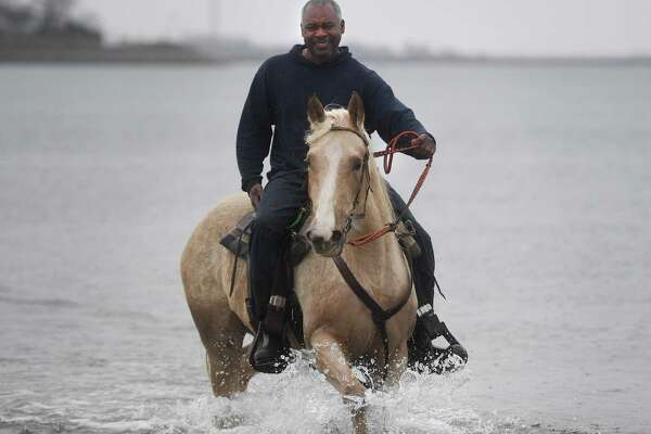 Despite a cold rain, Ricky Izzard, of Oxford, enjoys his final horseback ride of the season at Jennings Beach in Fairfield, Conn. on Sunday, March 31, 2019. Dogs and horses are allowed on Fairfield town beaches from October 1 until March 31.