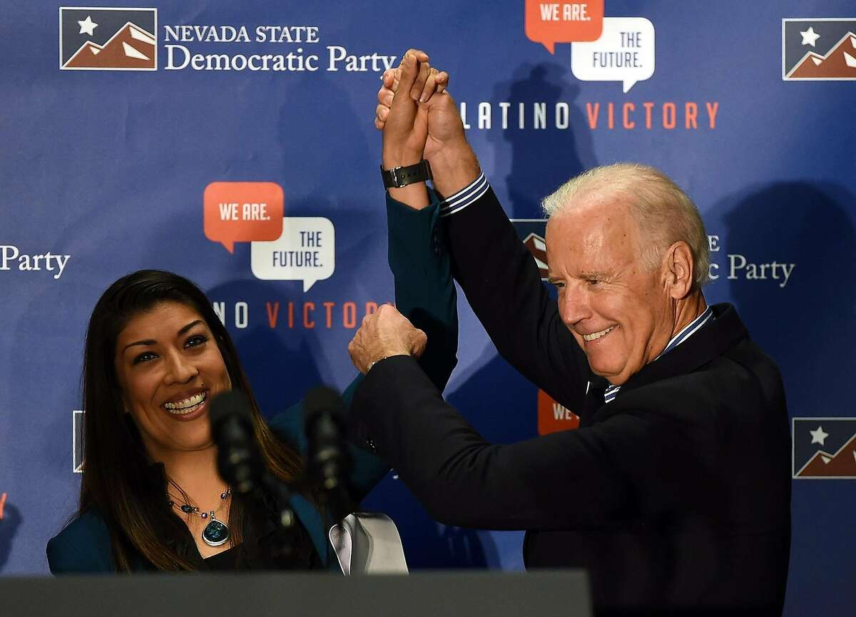 Then-Democratic candidate for lieutenant governor and Nevada Assemblywoman Lucy Flores, left, introduces U.S. Vice President Joe Biden at a get-out-the-vote rally at a union hall on Nov. 1, 2014 in Las Vegas, Nev. Flores wrote that she felt demeaned and disrespected when Biden touched her offstage at a 2014 campaign rally. She said she felt Biden's hands on her shoulders and froze. (Ethan Miller/Getty Images/TNS)