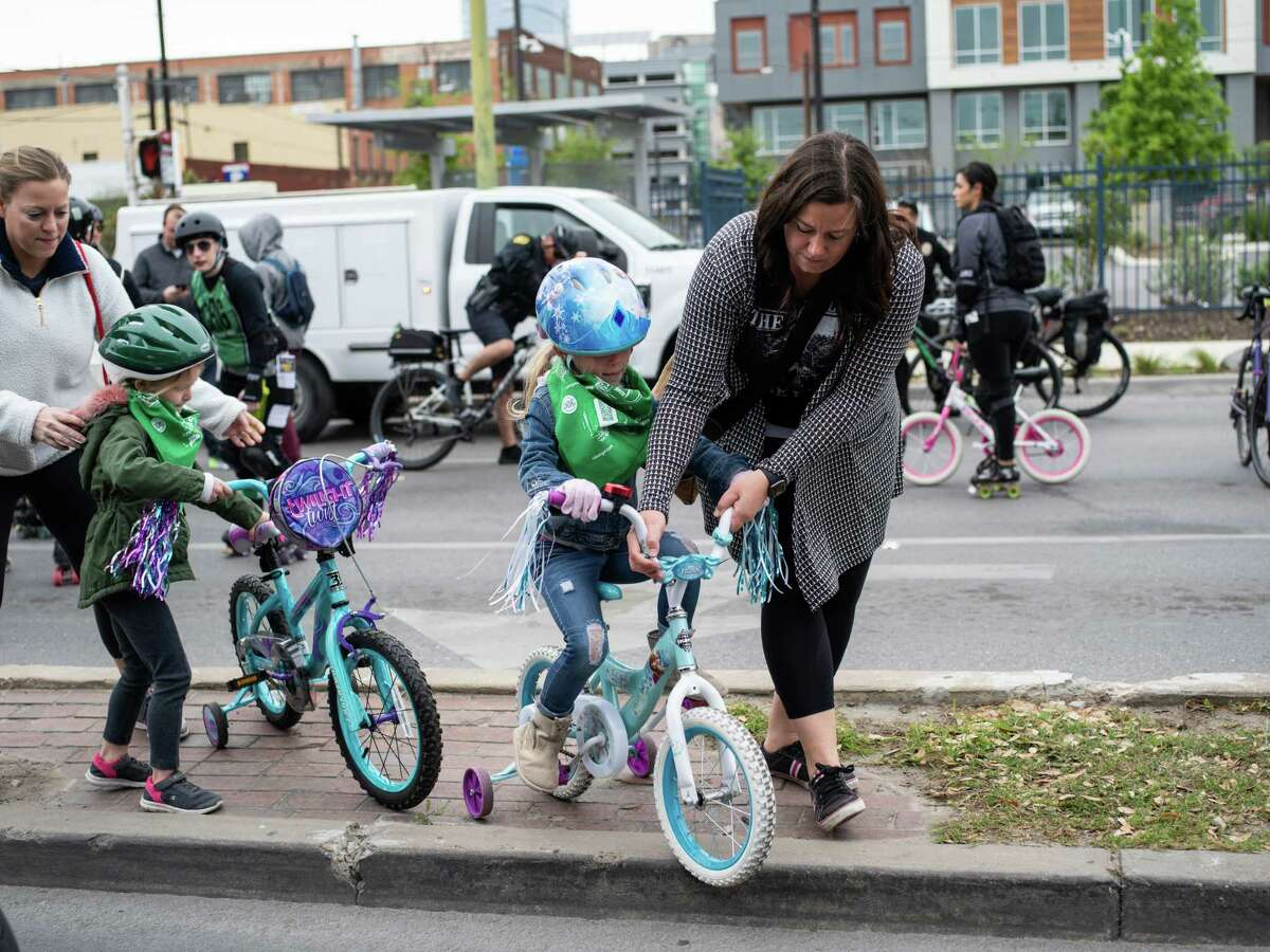 Jude Elliott, right, helps her friend's daughter Avery George, 6, center, to steer her bike as Avery's mother Tara George helps her other daughter Peyton George, 4, left, during the biannual Siclovia in downtown San Antonio on Sunday, March 31, 2019.