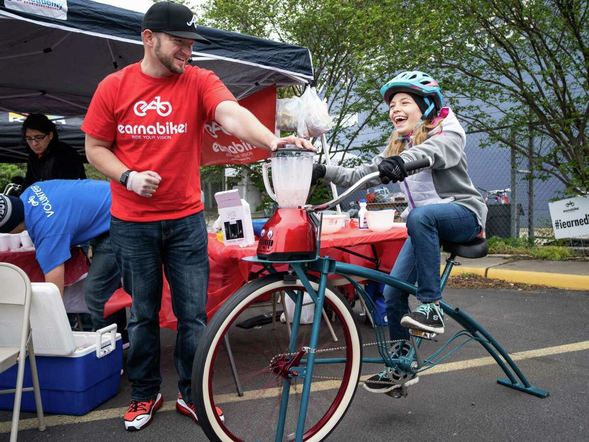 Claire Wenger, 9, right, pedals the stationary bike-powered blender to create her own banana-strawberry smoothie, held by Earnabike's Jon Rhoads, left, during the biannual Siclovia in downtown San Antonio on Sunday, March 31, 2019. Earnabike's community outreach program organized the event for Siclovia. Their program promotes street safety, community outreach and cycling.
