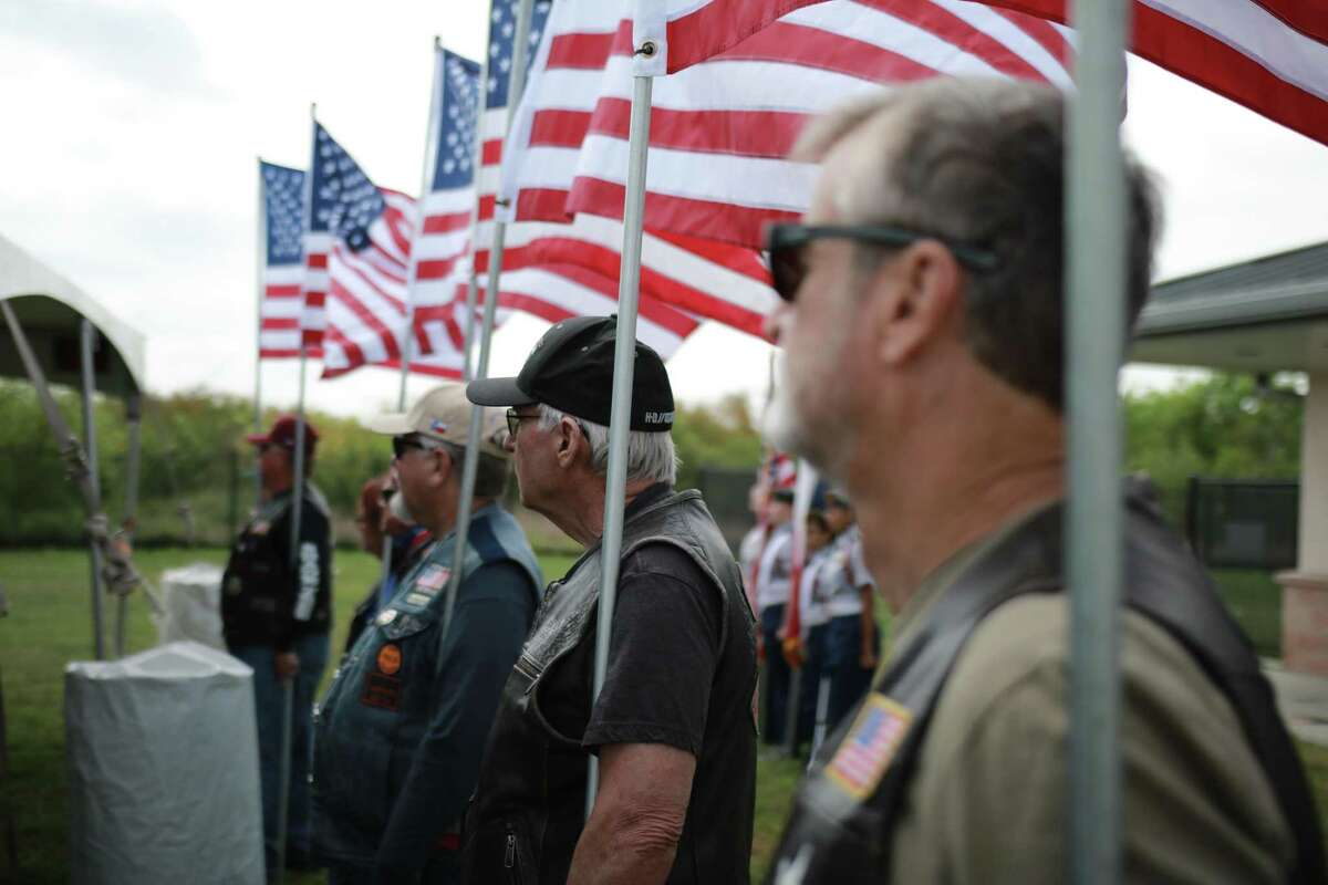 Members of the San Antonio chapter of the Patriot Guard Riders hold American flags at the Animal Care Services campus during the announcement of the Petco Founation K9s For Warriors Center next to ACS shelter.