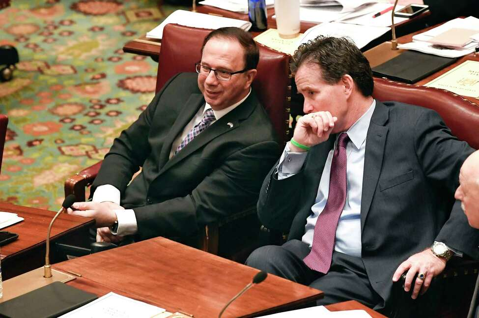 Senate Deputy Minority Leader Joseph Griffo, R-Utica, left, speaks with Senate Minority Leader John Flanagan, R-Smithtown, as Senate members debate budget bills in the Senate Chamber at the state Capitol Sunday, March, 31, 2019, in Albany, N.Y.