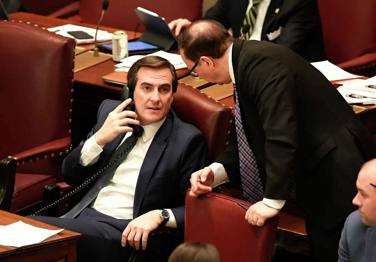 Senator Deputy Majority Leader, Michael Gianaris, D-Astoria, left, talks with Senate Deputy Minority Leader Joseph Griffo, R-Utica, as Senate members debate budget bills in the Senate Chamber at the state Capitol Sunday, March, 31, 2019, in Albany, N.Y.