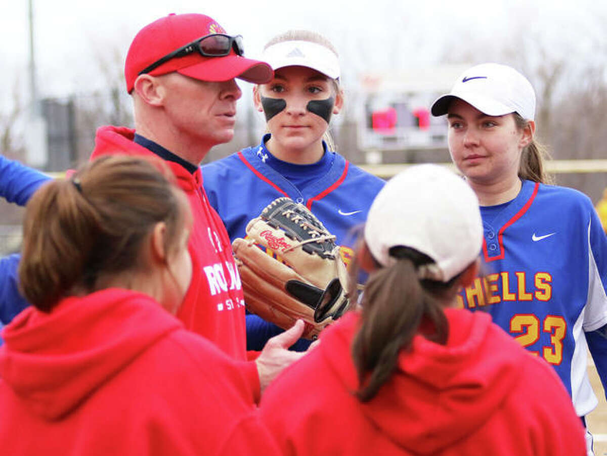 Roxana's Taylor Pickett (23) and Abi Stahlhut (middle) focus on coach Wade Stahlhut's message before taking the field in the sixth inning of a Shells victory March 20 in Bethalto.
