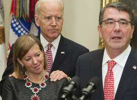 (FILES) In this file photo taken on February 17, 2015,  Secretary of Defense Ashton Carter (R) speaks beside his wife Stephanie and US Vice President Joe Biden during a swearing-in ceremony in the Roosevelt Room of the White House in Washington, DC. - Joe Biden, who is leading polls for the Democratic presidential nomination, on Friday , March 29, 2019 faced a misconduct accusation by a Nevada ex-lawmaker claiming the then-vice president inappropriately kissed her before a campaign event. Lucy Flores, the state's Democratic nominee for lieutenant governor in 2014, said she was beside the stage awaiting her turn to address a rally when Biden put his hands on her shoulders from behind, then leaned in and smelled her hair. (Photo by Saul LOEB / AFP)SAUL LOEB/AFP/Getty Images