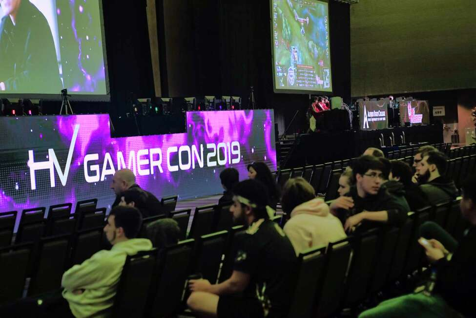 Adults and children watch college teams compete in video games at the HV Gamer Con 2019 at the Albany Capital Center on Sunday, March 31, 2019, in Albany, N.Y. The esports event brought in 19 college teams to compete against each other in the video games, Fortnite, League of Legends and Overwatch. Over 400 games took part in the event which was held Saturday and Sunday. (Paul Buckowski/Times Union)