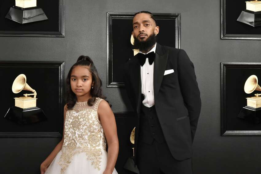 FILE - Emani Asghedom and Nipsey Hussle attend the 61st Annual Grammy Awards at Staples Center in this February 10, 2019 file photo in Los Angeles.According to the Los Angeles Police Department, Hussle was shot in front of his Los Angeles store on Sunday, March 31, and has died at age 33, according to multiple reports.