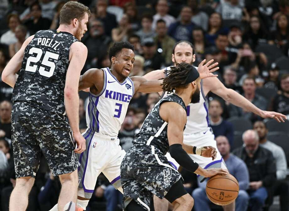 San Antonio Spurs' Patty Mills, front right, drives around Sacramento Kings' Yogi Ferrell (3) as he is screened by Spurs' Jakob Poeltl (25) during the first half of an NBA basketball game, Sunday, March 31, 2019, in San Antonio. (AP Photo/Darren Abate) Photo: Darren Abate/Associated Press