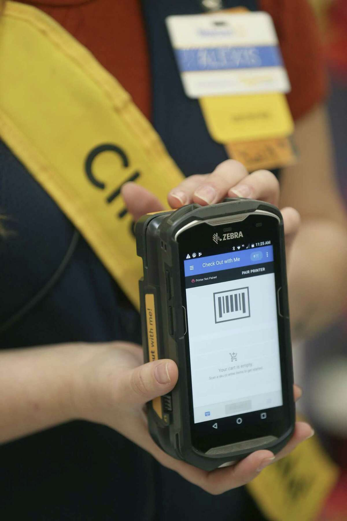 """Alexis Byrd shows her hand-held check-out device Feb. 26, 2019 at the New Braunfels Walmart Supercenter that is used to check-out customers before they even get in line. The program that Walmart called """"Check Out with Me"""" is one of the pieces of technology the company says it is using to improve shopping experiences in their stores."""
