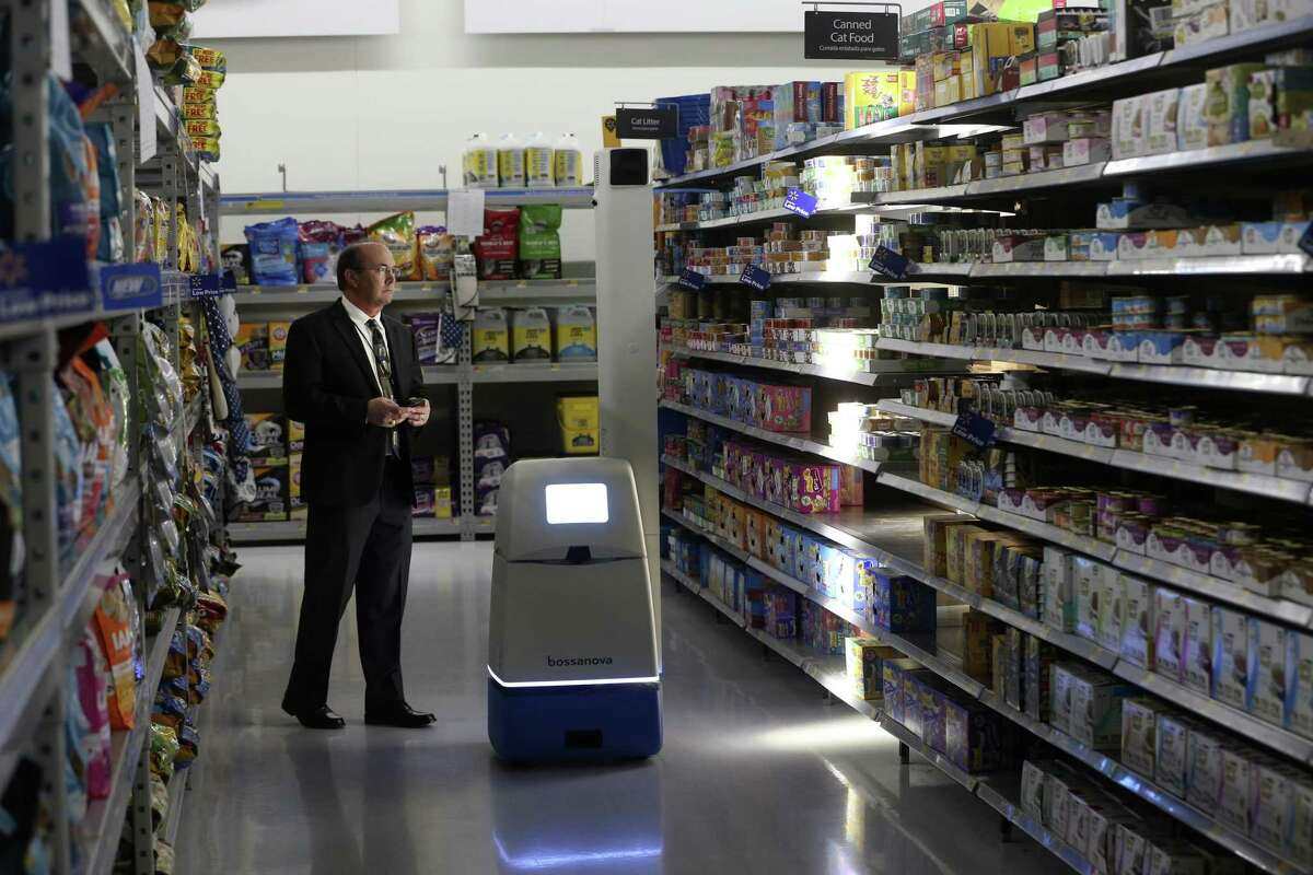 David Drastata, Walmart marketing manager, watches an autonomous machine scan shelves Feb. 26, 2019 at the New Braunfels Walmart Supercenter. The inventory-checking machine is one of the pieces of technology Walmart says it is using to improve shopping experiences in their stores.