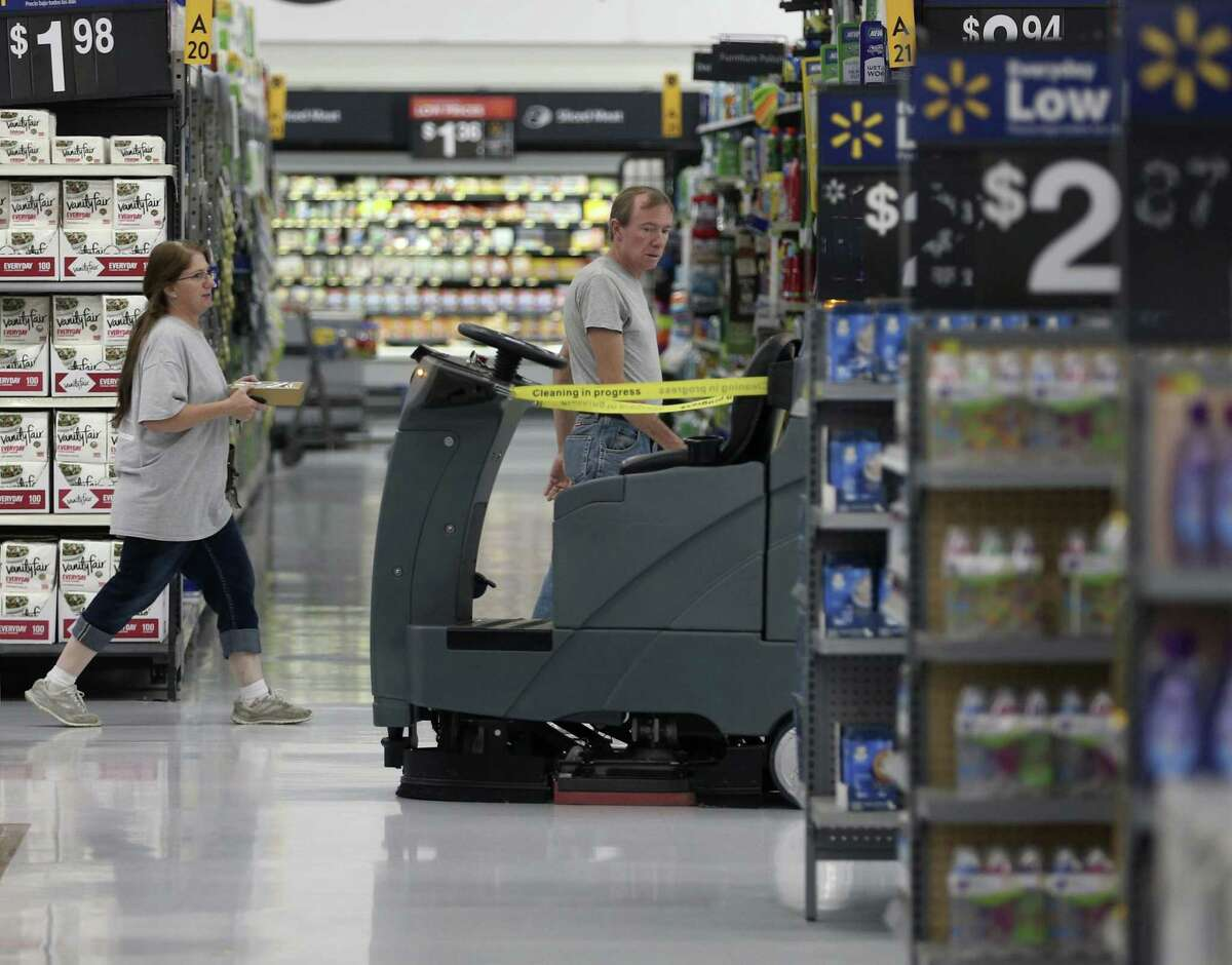 Customers walk Feb. 26, 2019 at the New Braunfels Walmart Supercenter past an automated floor cleaner that uses preprogramed routes and onboard sensors to navigate the store while it cleans. The machine is one of the pieces of technology Walmart is using to improve shopping experiences in their stores.