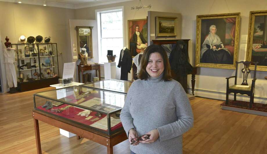 Lisa Roush, curator for the New Milford Historical Society, stands among the society's newest exhibit. On display are select clothes and accessories from their permanent collection on March 22 in New Milford. Photo: H John Voorhees III / Hearst Connecticut Media / The News-Times