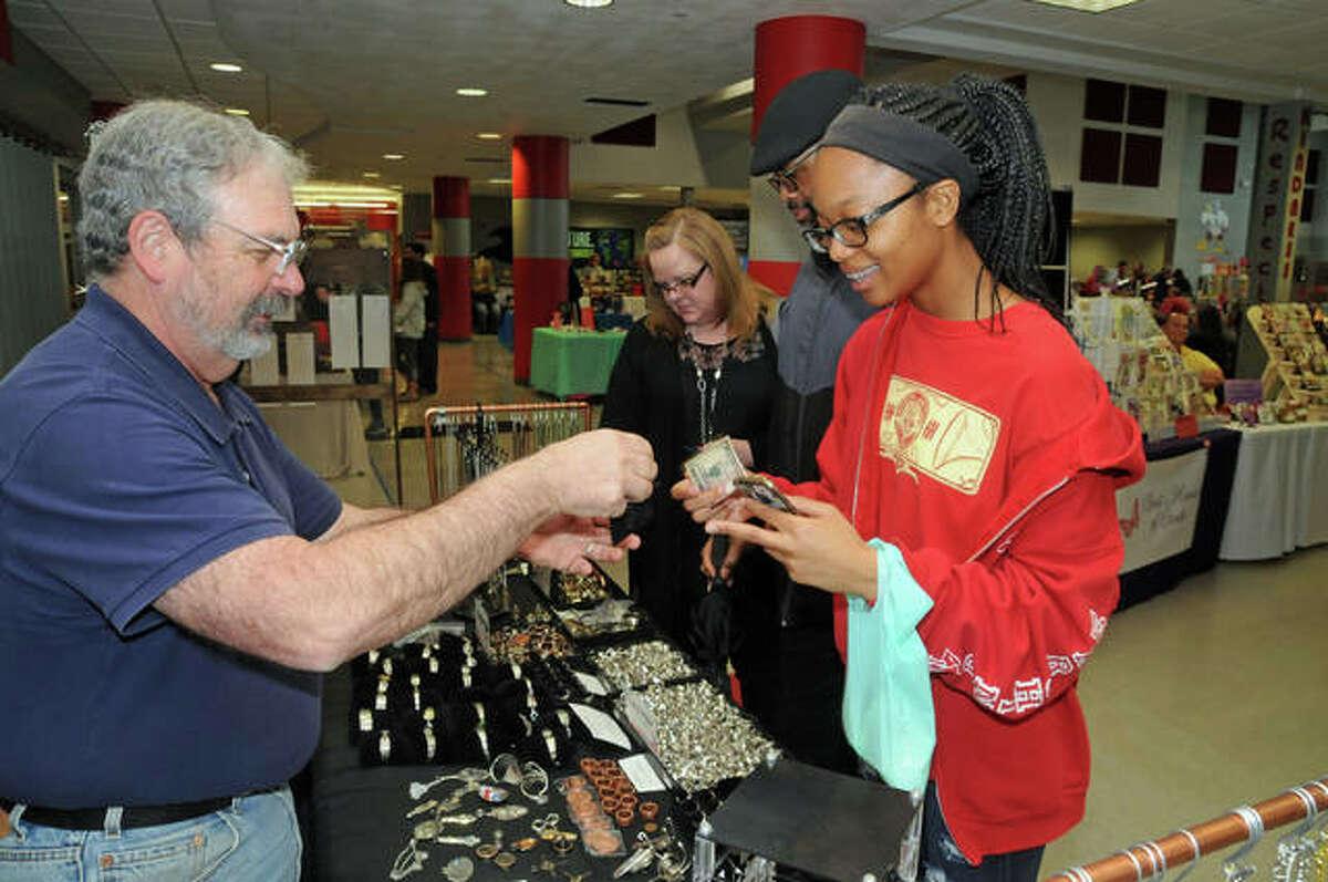 David Totten, of Godfrey, makes a sale to Nina Womack, of Alton, at the Olde Alton Vendor & Craft Fair Saturday at Alton High School.