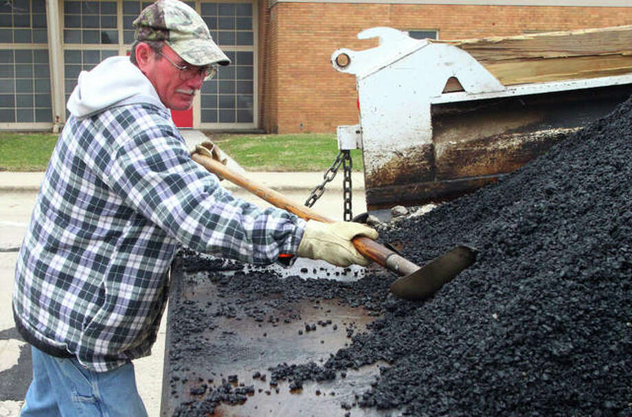 Earl McMeans with the Jacksonville Street Department fills potholes Friday along Morgan Street. Photo: Rosalind Essig | Journal-Courier