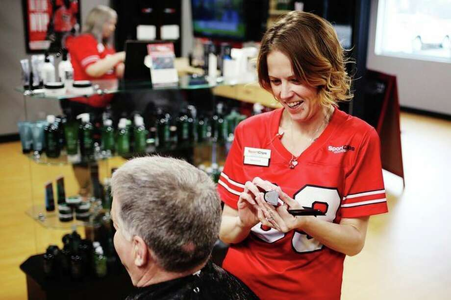 Melissa Merritt chats with a customer while giving him a haircut at SportClips on Thursday, March 21. For more photos, go to www.ourmidland.com. (Katy Kildee/kkildee@mdn.net)