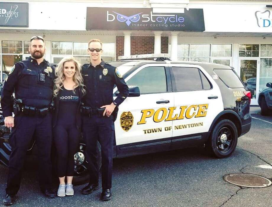 Newtown police officers with Boostcycle owner Emily DeMarco on March 30, 2019. Photo: Contributed Photo / Facebook