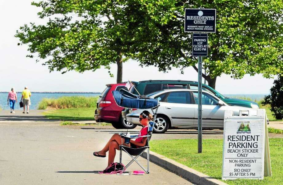 In this Register file photo, Alyssa Talamelli of West Haven, right, a City of West Haven constable at the time, monitors resident parking beach stickers at the parking lot at the Bradley Point on Ocean Avenue in West Haven in July 2014. Photo: Hearst Connecticut Media File