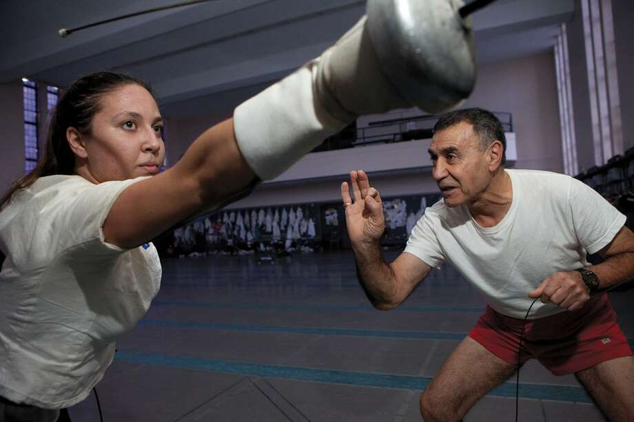 Former Yale University fencing coach Henry Harutunian instructs épéeist Alexia Cesar, class of 2012, in this 2010 photo from the Yale Alumni Magazine. Harutunian was fired March 28, 2019, after 49 years coaching Yale fencing. Photo: Contributed Photo / Julie Brown / ©2010 Julie Brown Photography All Rights Reserved