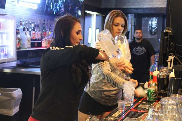 Torinos PizzaBar bartender Nikki Bishop, left, prepares a mixed drink with server Rachel Volcheck lending a hand.