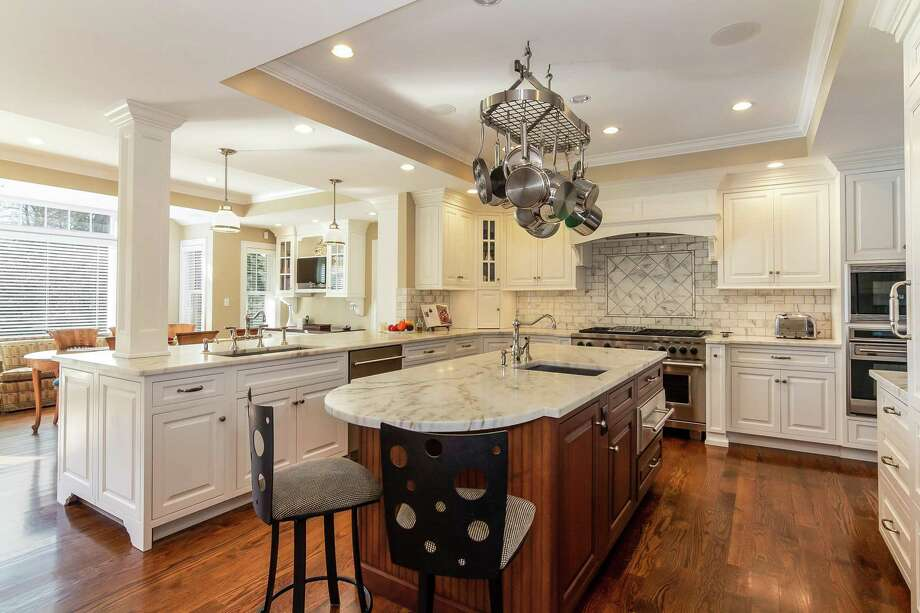 Kitchen amenities at 129 Davis St. in Hamden include custom cabinetry, honed marble countertops, an island with breakfast bar and state-of-the-art appliances, including SubZero refrigerator and freezer, Wolf gas range and wall oven and warming drawer. Photo: Press|Cuozzo / © 2019 PlanOmatic