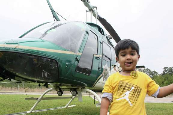 Harris Ahmad, 3, stands beside a helicopter from the Harris County Sheriff's Department parked beside the Masjid Al Salam mosque in Spring on March 30, 2019.