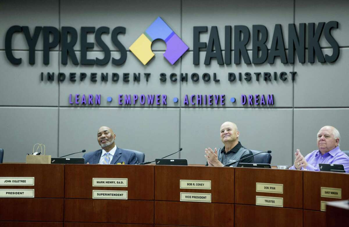 Dr. John Ogletree, Jr., board president, left, Dr. Mark Henry, and board member Bob Covey applaud after a group of students were recognized during the Cypress-Fairbanks ISD school board of trustees meeting on Thursday, June 14, 2018, in Cypress. ( Brett Coomer / Houston Chronicle )