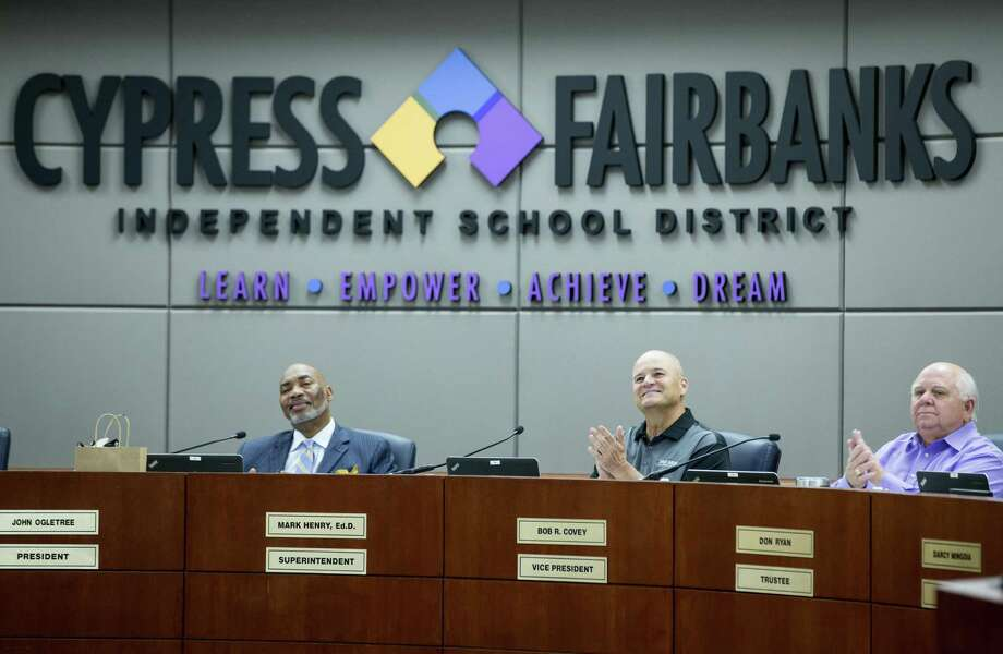 Dr. John Ogletree, Jr., board president, left, Dr. Mark Henry, and board member Bob Covey applaud after a group of students were recognized during the Cypress-Fairbanks ISD school board of trustees meeting on Thursday, June 14, 2018, in Cypress. ( Brett Coomer / Houston Chronicle ) Photo: Brett Coomer, Staff Photographer / Houston Chronicle / © 2018 Houston Chronicle
