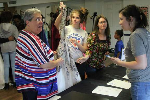 Emily Cook helping customers at the 5th Annual Dress Extravaganza by the 27 Dresses Project was a success on March 29-30 at Fellowship Hall of First United Methodist Church in Cleveland.