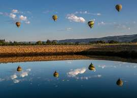 FILE - A group of hot air balloons float above the Napa Valley on Oct. 15, 2015, in Yountville, Calif.