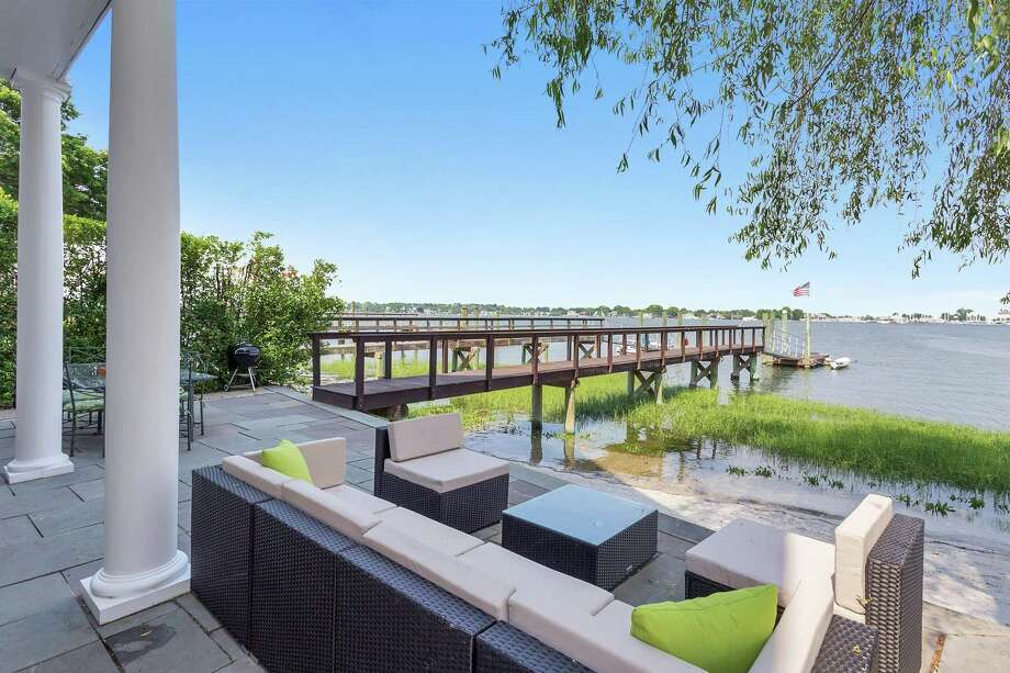 The waterfront home at 5 Seabreeze Place in Norwalk has a partially covered terrace, a pier, an attached floating dock and low-maintenance landscaping with oyster shells, sea grasses and pink roses. Photo: Halstead Real Estate / ONLINE_CHECK
