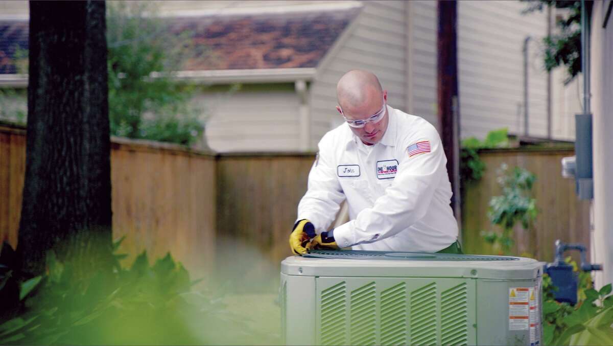 A One Hour Air Conditioning & Heating employee works on an air conditioner unit. Childress, the general manager, recommends annual maintenance of your unit.