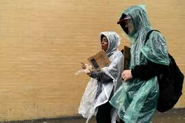 Homeless youth Chase McNamara, 22, and Alexis Jefferson, 18, walk in the rain towards Powell St. to busk for change, in San Francisco, CA Monday, December 21, 2015.