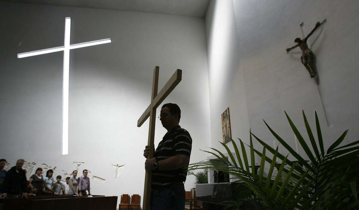 Jay Russell holds a cross during at St. Basil Chapel at St. Thomas University during a service prior to the start of the Way of the Cross Good Friday procession in 2010. The university's annual I-Fest is set for April 4.