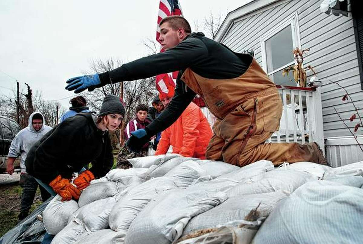 Sky Coleman (left) stacks a sandbag while Tyler Hopkins awaits another Saturday as a group of 15 middle and high school students from Louisiana, Missouri, sandbag the home of the aunt of a fellow student in Clarksville, Missouri. The Mississippi River entered major flood stage on Saturday for the first time this spring.