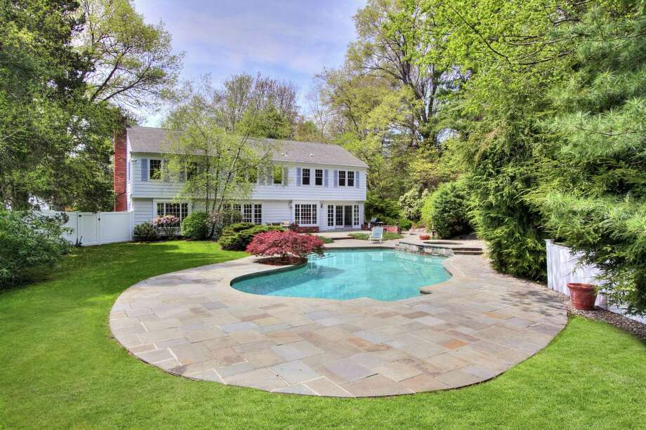 The colonial at 4 Parsons Walk is on a Darien cul-de-sac and the 1.15-acre lot boasts a terrace and a private pool area that includes a spa. Photo: The Hawes Team At Halstead Connecticut / ONLINE_CHECK