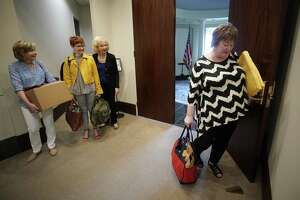 Nancy Lisenby, chief of staff assistant, left, Laura Cather Pears, director of scheduling, and Mary Sage, office manager, wait as Jean Becker, chief of staff, right, closes the door to the George H.W. Bush office on Memorial Drive Friday, March 29, 2019, in Houston. The staff closed the office for the last time on Friday. The George and Barbara Bush Foundation will occupy part of the office space.