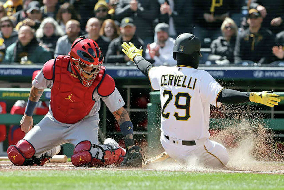 The Pirates' Francisco Cervelli (29) ahead of the tag by Cardinals catcher Yadier Molina on a double by Colin Moran in the first inning of Monday's game in Pittsburgh.