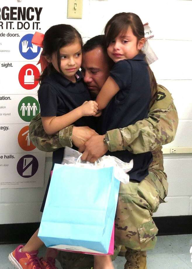 Bailey and Emily Valdez hug their father upon his unannounced arrival at the Muller Elementary library. As March came to a close, a welcome home celebration transpired at Muller Elementary when Sgt. Robert Valdez dropped by the campus library to surprise his two daughters. Valdez had just returned from his nine-month deployment with the U.S. National Guard. The reunion also included his wife, Kimberly Valdez, and infant son, Robert. Photo: United ISD /Courtesy Photo