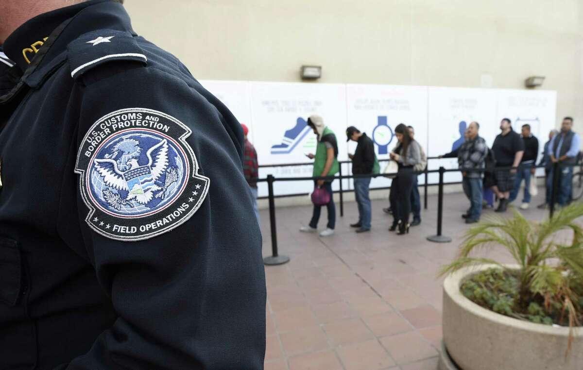 ARCHIVO - En esta imagen del 10 de diciembre de 2015, personas cruzan a pie la frontera desde México hacia Estados Unidos en el Puerto de Entrada de Otay Mesa en San Diego.
