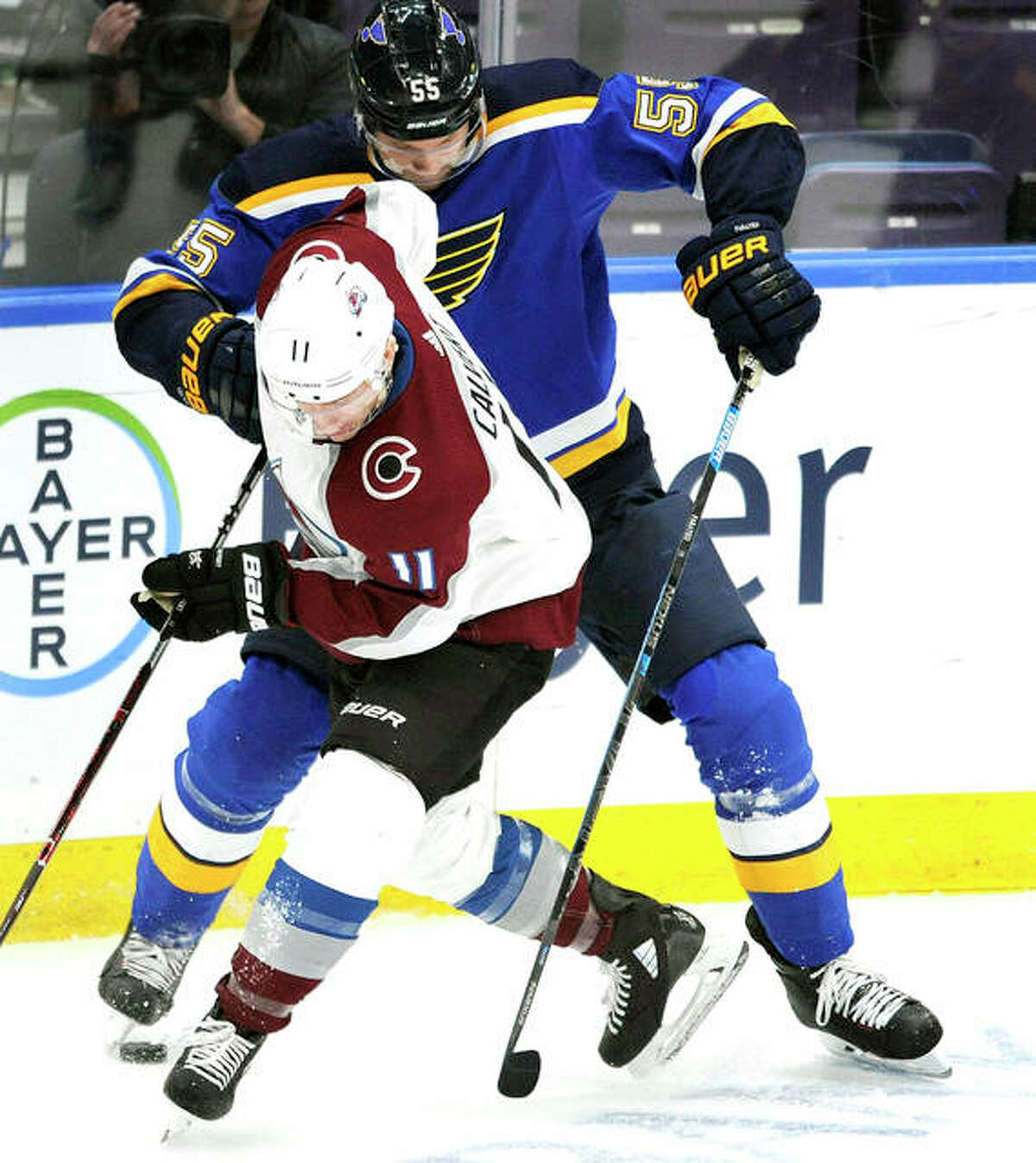 The Blues' Colton Parayko (55) battles for the puck with Colorado's Matt Calvert (11) in the second period of Monday night's game in St. Louis.