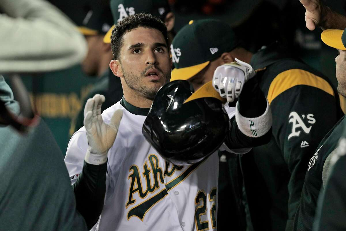 Ramon Laureano (22) high fives teammates in the dugout after hitting his third inning solo homerun as the Oakland Athletics played the Boston Red Sox at the Coliseum in Oakland, Calif., on Monday, April 1, 2019.