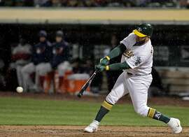 Kendrys Morales (12) hits a single in the eighth inning as the Oakland Athletics played the Boston Red Sox at the Coliseum in Oakland, Calif., on Monday, April 1, 2019.