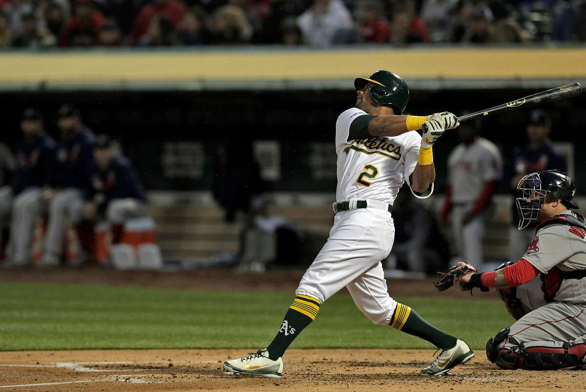 Designated hitter Khris Davis (2) watches his solo homerun in the second inning as the Oakland Athletics played the Boston Red Sox at the Coliseum in Oakland, Calif., on Monday, April 1, 2019.
