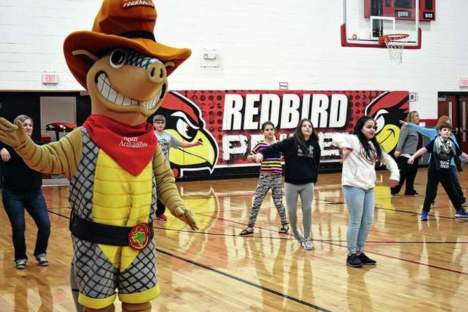 Texas Roadhouse mascot Andy the Armadillo helps teach students how to line dance Monday at Virginia Elementary School. The chain restaurant's Springfield location will help raise funds for the school by donating a portion of today's proceeds to the school. Photo: Samantha McDaniel-Ogletree | Journal-Courier