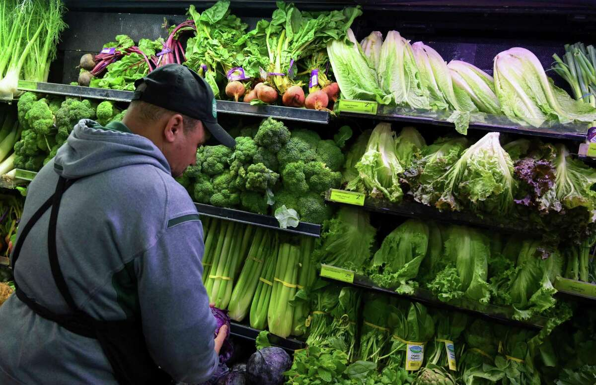 A produce worker stocks shelves in November 2018 at a Whole Foods Market in Washington, D.C.