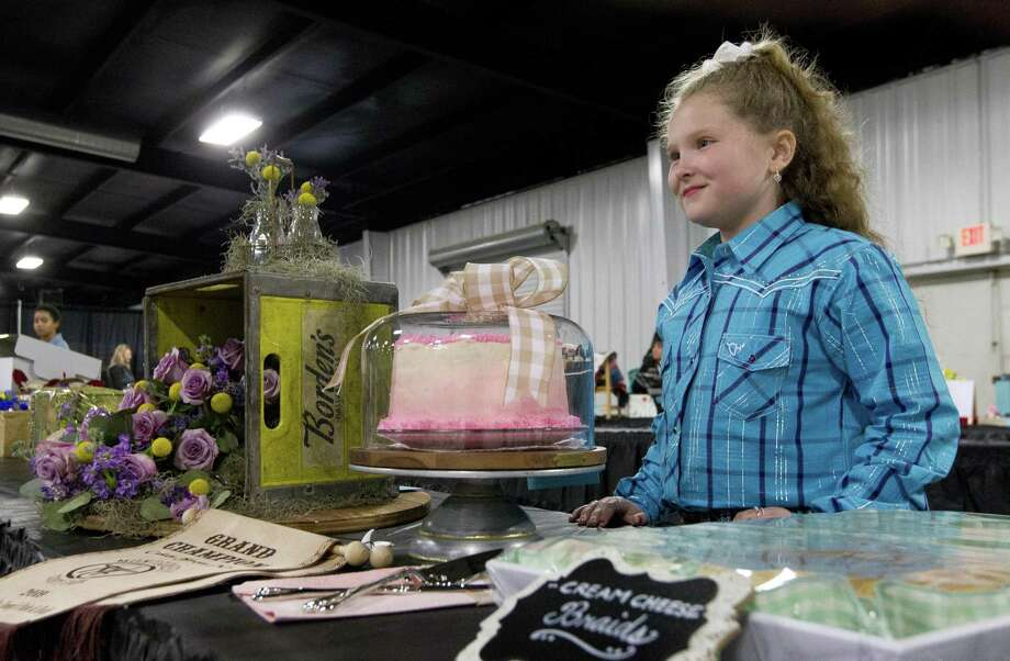 Homeschooler Brynn Coy, 9, shares a laugh beside her grand champion cakes before the non-livestock auction at the Montgomery County Fair and Rodeo on Monday in Conroe. Photo: Jason Fochtman, Houston Chronicle / Staff Photographer / © 2019 Houston Chronicle