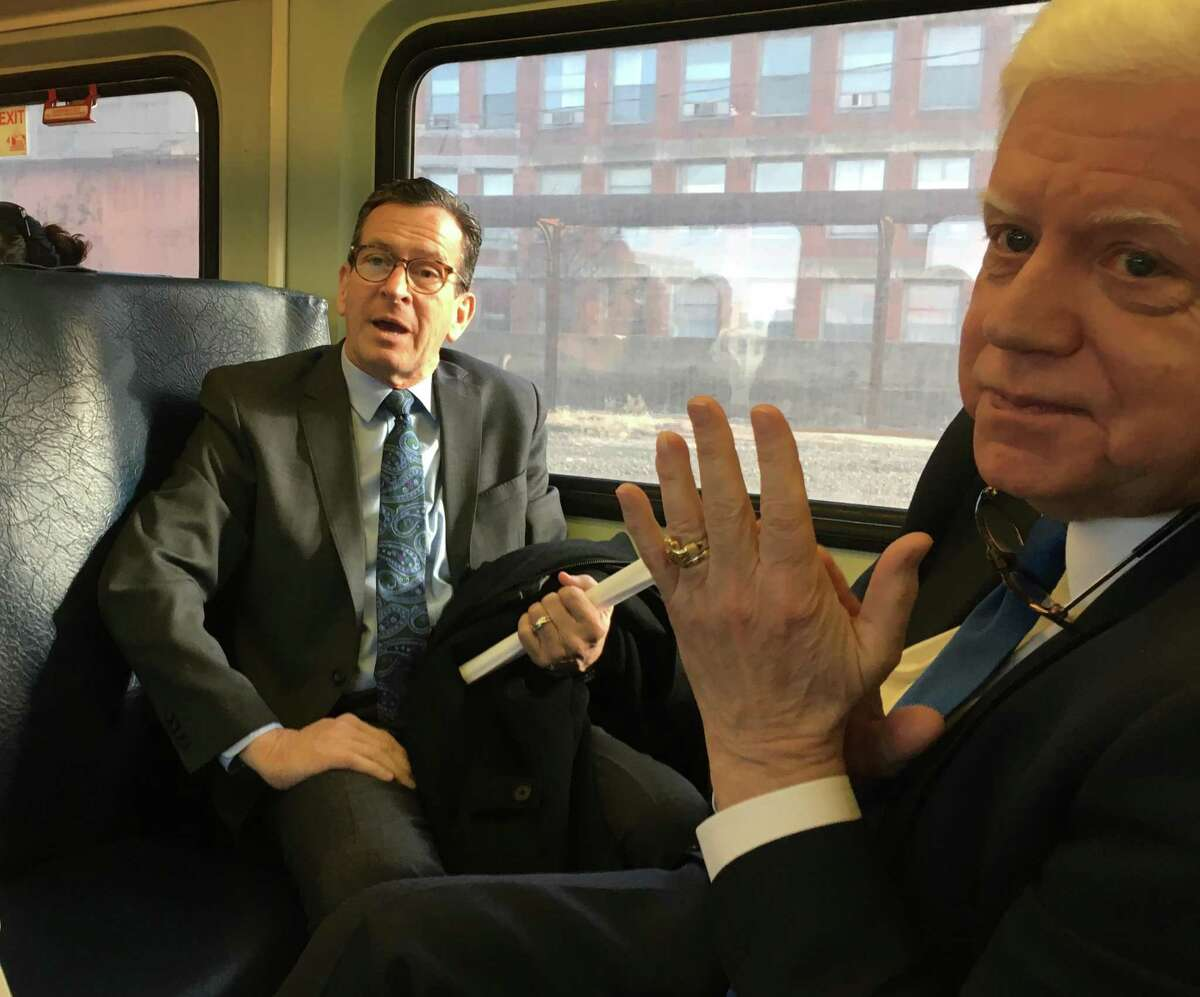 Former Gov. Dannel P. Malloy, left, takes his first ride on the CTRail commuter train from Hartford to Springfield, Mass., in December. At right is U.S. Rep. John B. Larson, D-1st District. The rail line cost $769 million to upgrade and $43 million a year to run but it connects New Haven, Hartford and Springfield with multiple daily round trips.