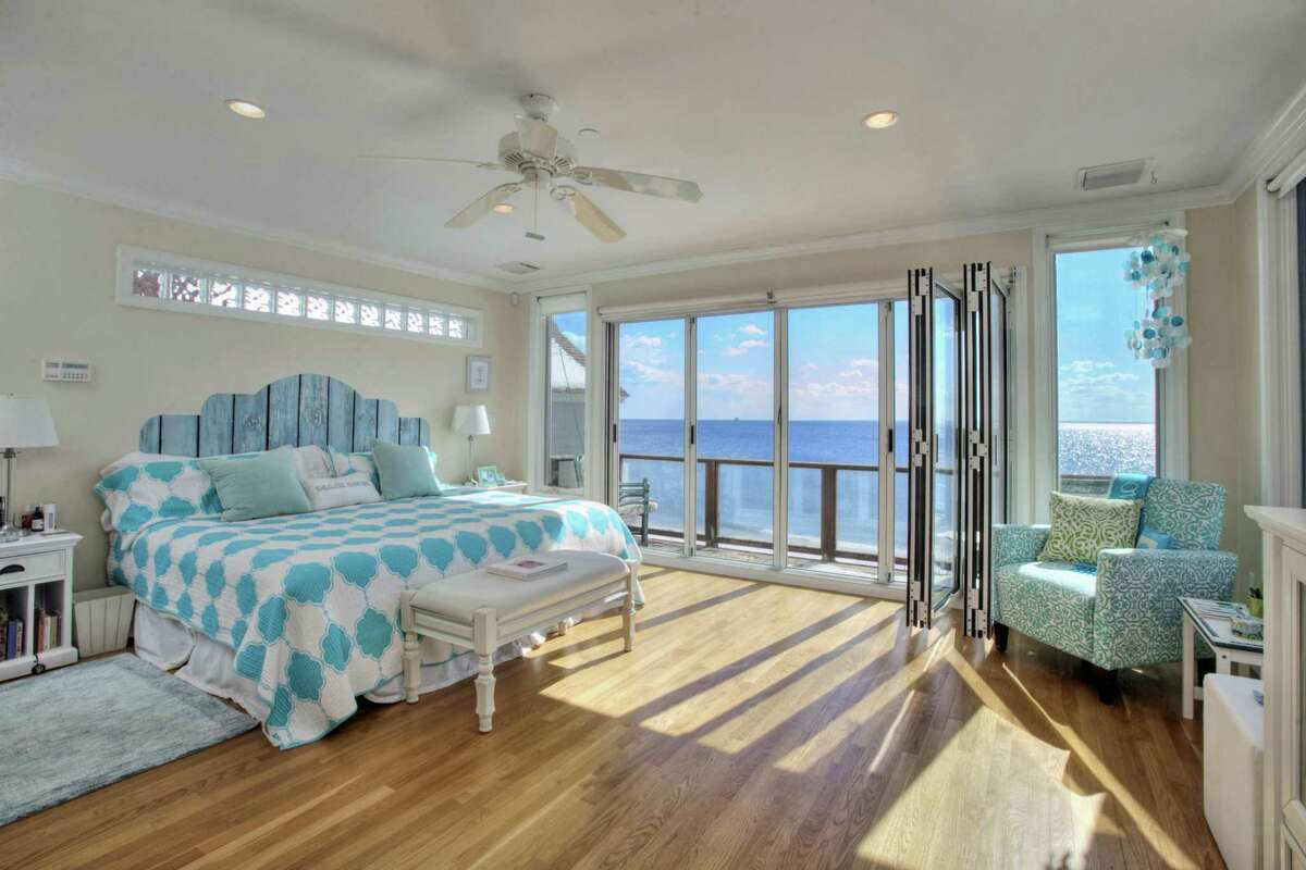 The master bedroom suite features a wall of floor-to-ceiling windows that open, accordion-style, to a private balcony/deck looking over the Sound.