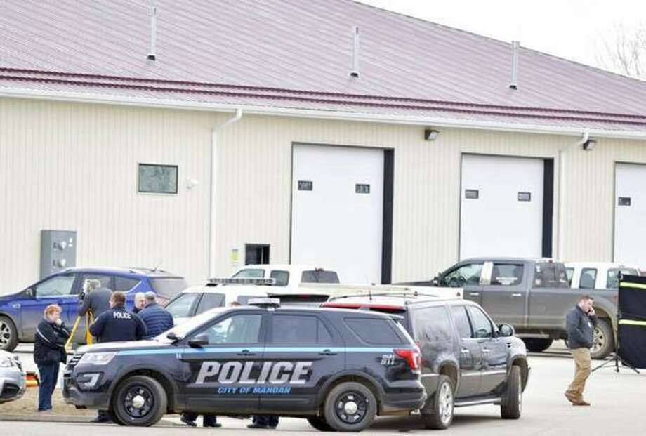 Mandan, N.D. Police Deputy Chief Lori Flaten, left, and other law enforcement personnel stand outside the scene on the south side the RJR Maintenance and Management property in Mandan, N.D., on Monday.